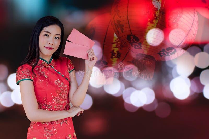Aziatische vrouw die rode traditionele kleding dragen die rode zak met de Chinese nieuwe achtergrond van het jaarfestival met lan stock afbeelding