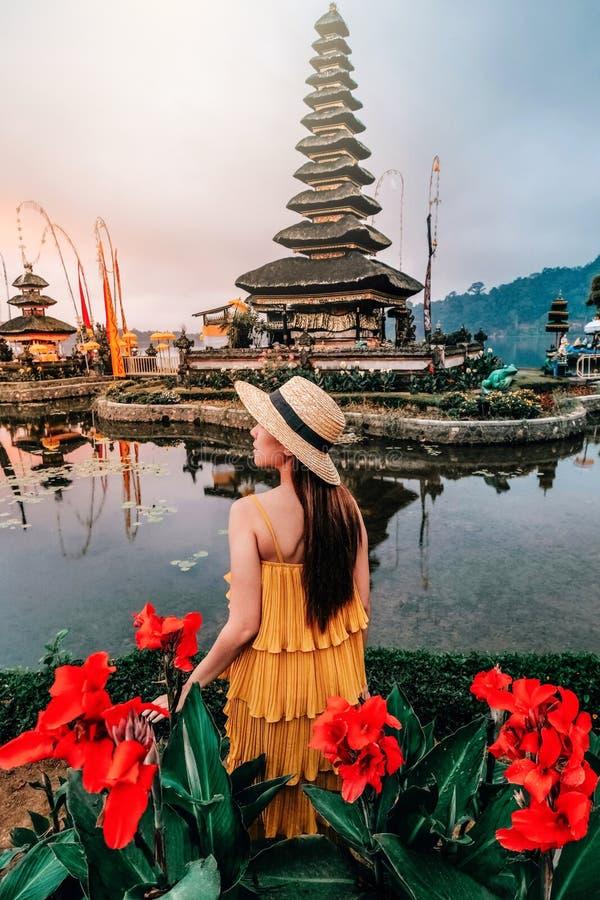 Aziatische vrouw die 's morgens bij Pura Ulun Danu Beratan de Floating Temple in Bali, Indonesië, op reis is stock foto's