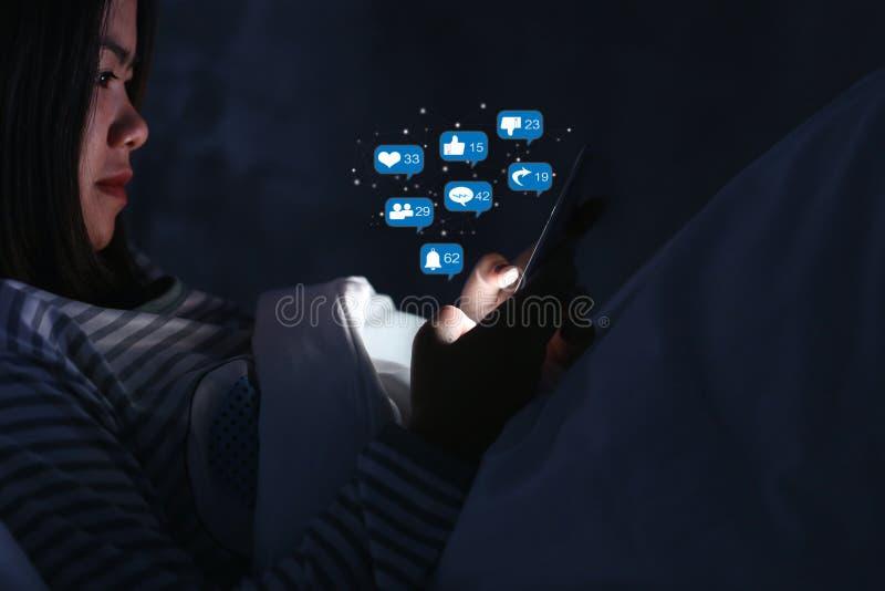 Aziatische vrouw die smartphone voor het controleren van sociale media met pictogram of hologram bij nacht op het bed in donkere  stock afbeelding