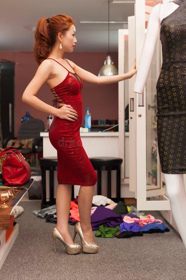 Aziatische vrouw die spiegel het winkelen het kiezen kijken stock foto's
