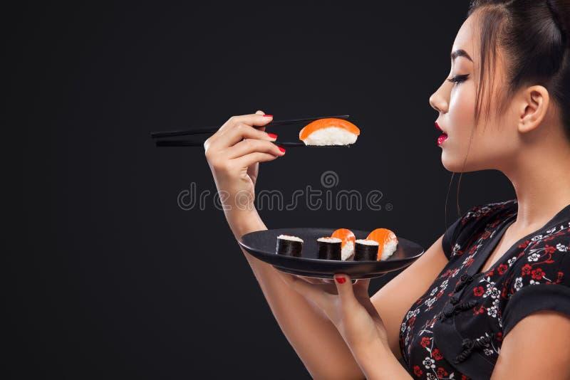 Aziatische vrouw die sushi en broodjes op een zwarte achtergrond eten stock foto's