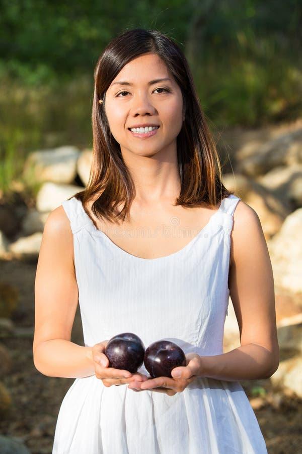 Aziatische vrouw die terwijl het houden van pruimen glimlachen stock afbeelding