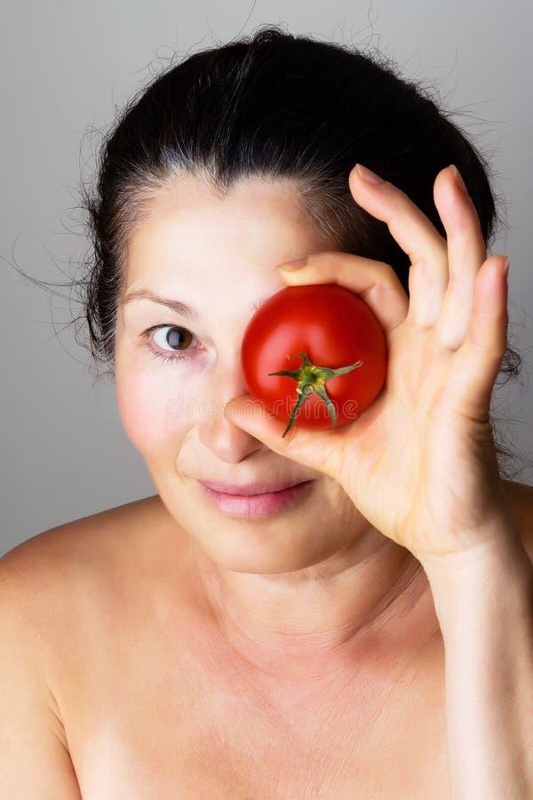 Aziatische vrouw die tomaten tonen royalty-vrije stock foto