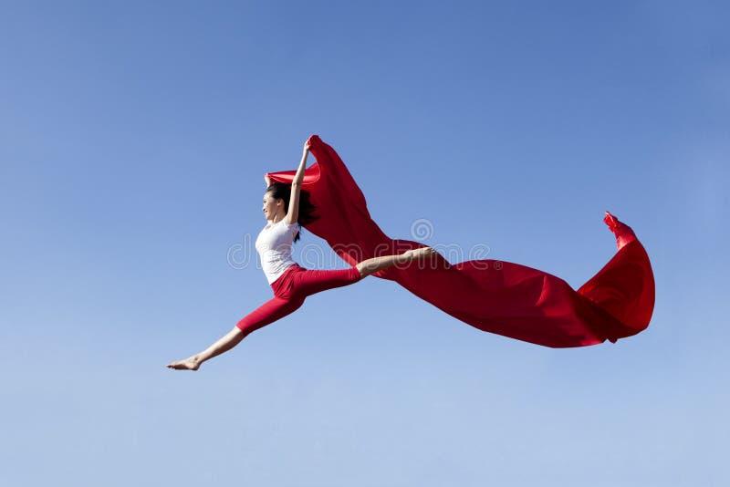 Aziatische vrouw die uitdrukkend vrijheid springt stock afbeeldingen