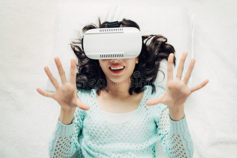 Aziatische vrouw die vr beschermende brillen dragen die op bed liggen stock foto's