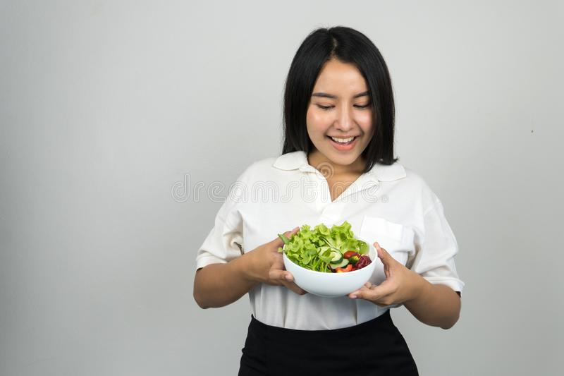 Aziatische vrouw die wit polooverhemd dragen en een kom salade houden royalty-vrije stock afbeelding