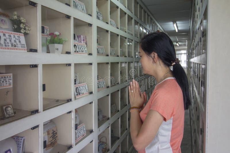 Aziatische vrouw die zich bij Chinese stijlcolumbarium bevinden die het bidden voor asurnen van voorvader betalen stock afbeeldingen