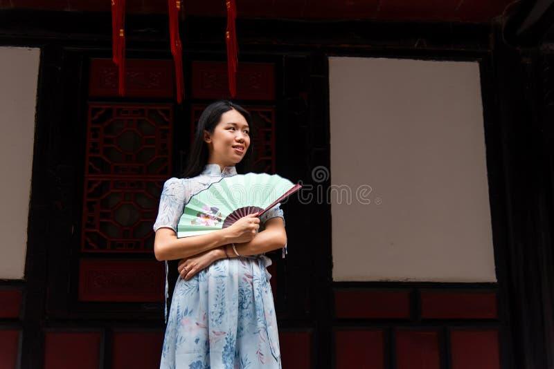 Aziatische vrouw in een tempel die een handventilator houden stock fotografie