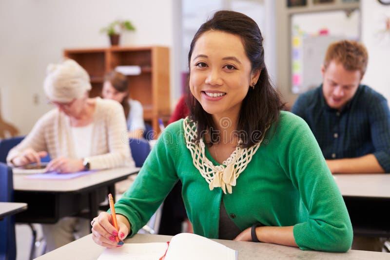 Aziatische vrouw in een volwassenenvormingsklasse die aan camera kijken stock afbeelding