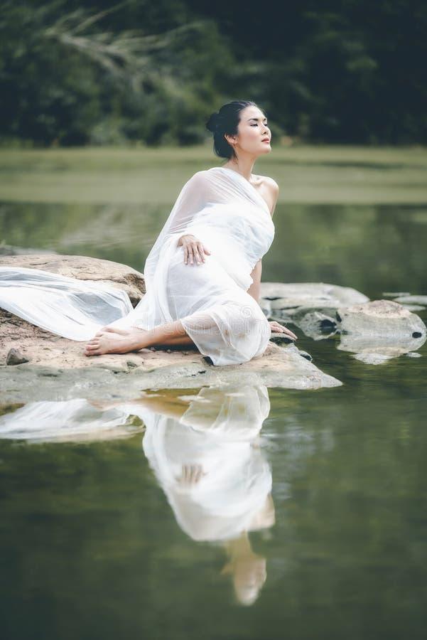 Aziatische vrouw in een witte badjas, die rakend water in st genieten van royalty-vrije stock afbeelding