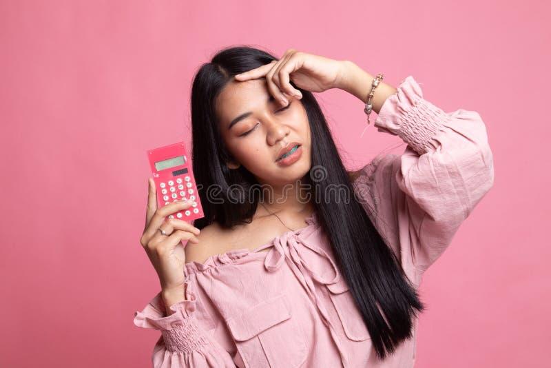 Aziatische vrouw geworden hoofdpijn met calculator stock afbeelding