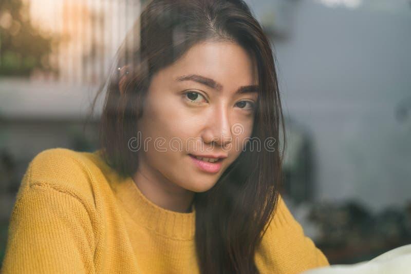 Aziatische vrouw het drinken koffie in koffiewinkel en het glimlachen royalty-vrije stock foto's