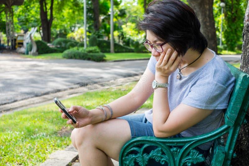 Aziatische vrouw het spelen smartphone in het park royalty-vrije stock fotografie