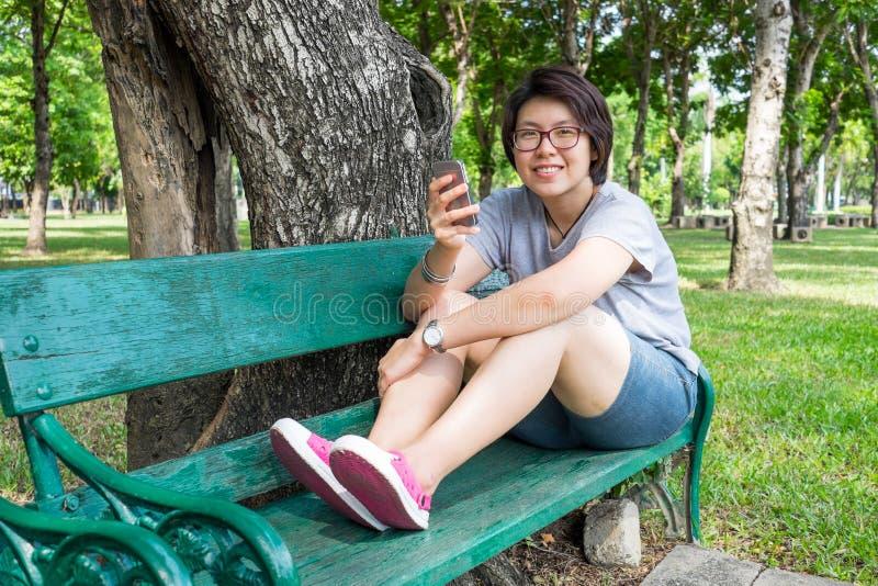 Aziatische vrouw het spelen smartphone in het park stock foto