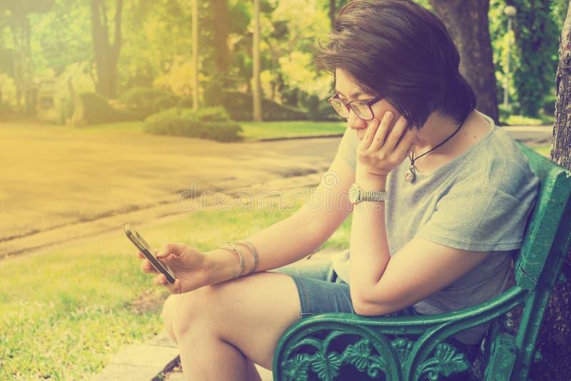 Aziatische vrouw het spelen smartphone in het park - uitstekend effect royalty-vrije stock foto's