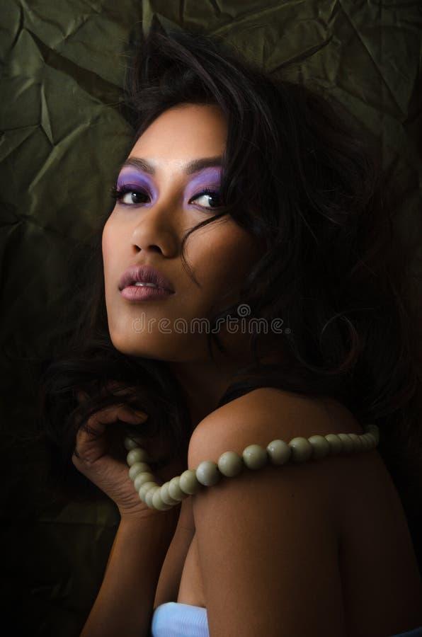 Aziatische vrouw met purpere samenstelling royalty-vrije stock afbeelding