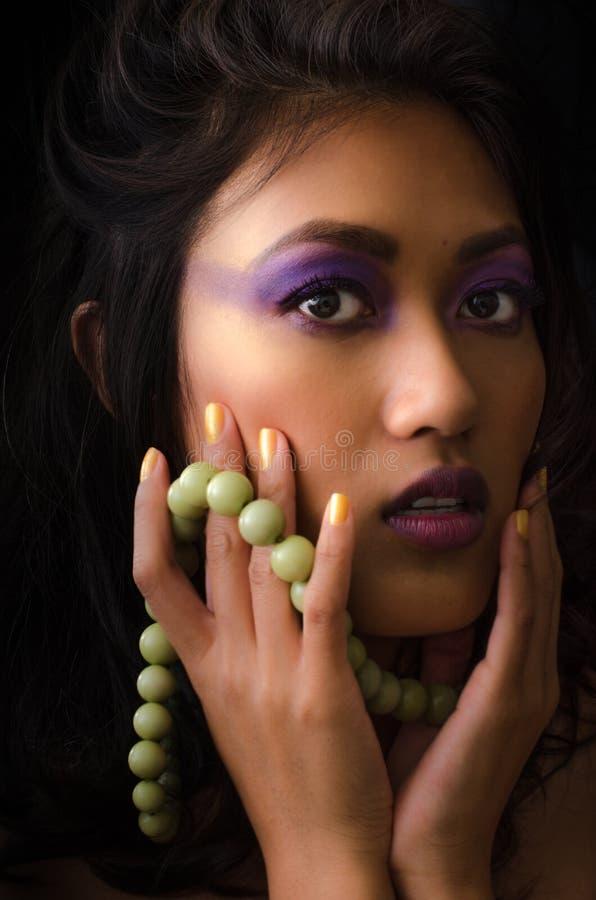 Aziatische vrouw met purpere samenstelling en groene halsband stock afbeeldingen