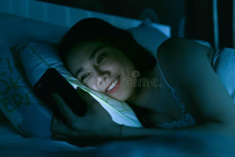 Aziatische vrouw op bed laat bij nacht die gebruikend mobiele telefoonband texting stock foto's