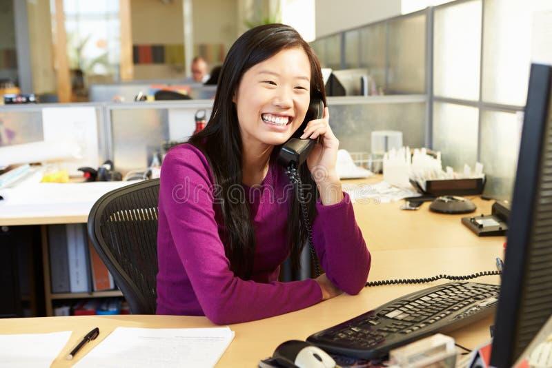 Aziatische Vrouw op Telefoon in Bezig Modern Bureau royalty-vrije stock fotografie