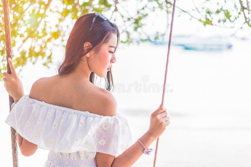 Aziatische vrouw op witte kledingszitting op schommeling bij strand Mensen en royalty-vrije stock afbeelding