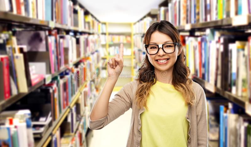 Aziatische vrouw of student met vinger omhoog bij bibliotheek stock afbeeldingen
