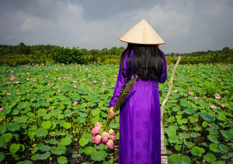 Aziatische vrouw in traditionele kleding met lotusbloembloem royalty-vrije stock afbeeldingen