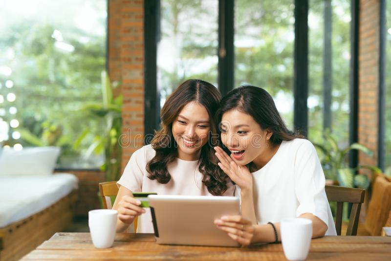 Aziatische vrouw twee die laptop voor het winkelen online met kredietauto met behulp van royalty-vrije stock afbeelding