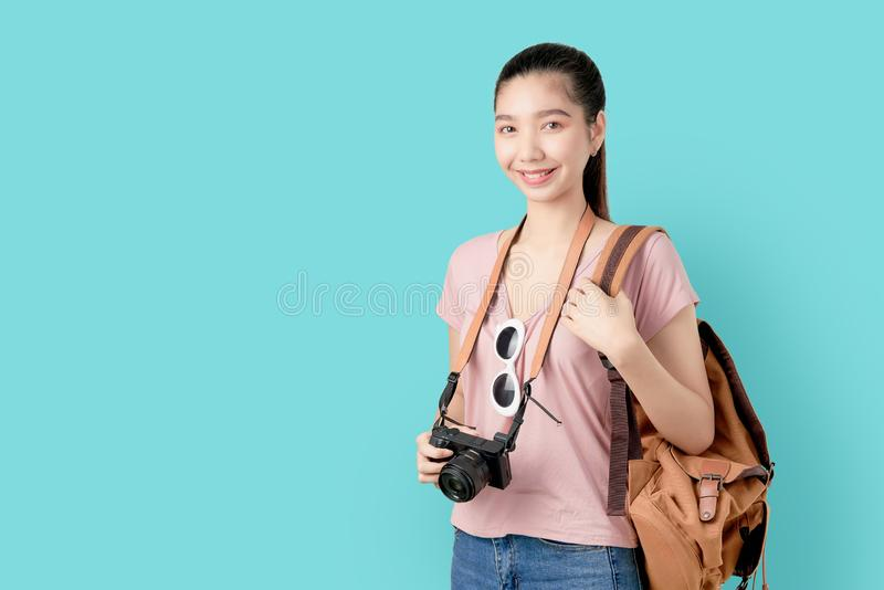 Aziatische vrouw van de portretglimlach de gelukkig klaar te reizen, toerisme en vakantie met rugzak, fotocamera op blauwe achter royalty-vrije stock afbeeldingen