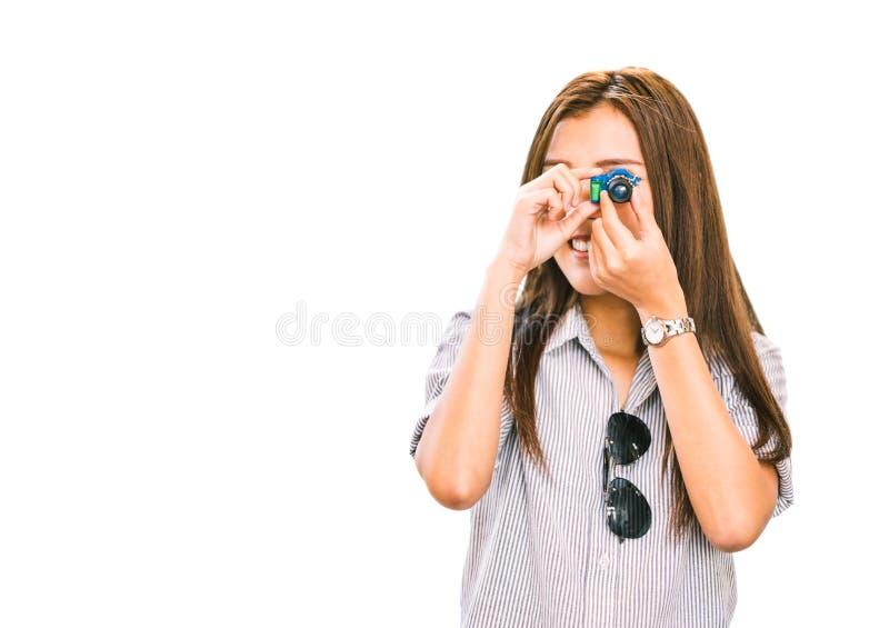 Aziatische vrouw of vrouwelijke reiziger die beeld met stuk speelgoed camera nemen, minicijfer keychain Geïsoleerdj op witte acht royalty-vrije stock fotografie
