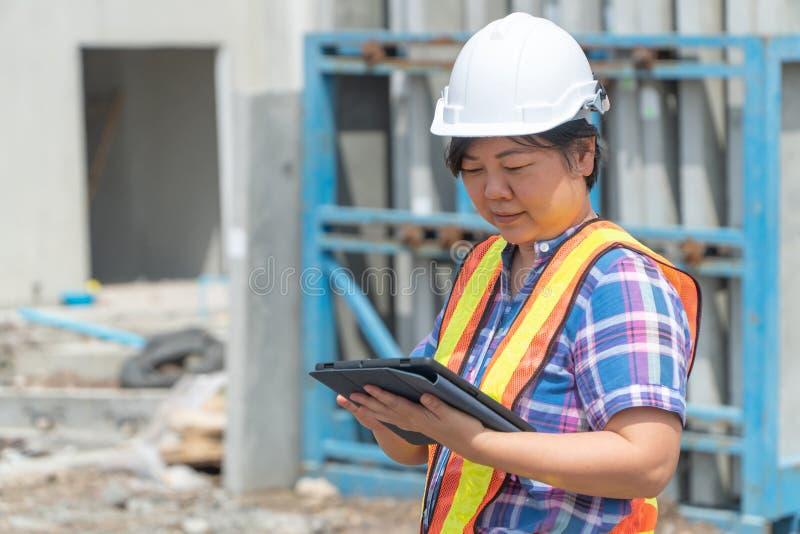 Aziatische vrouwelijke arbeider en ingenieur op de bouwplaats met behulp van een tablet om de nauwkeurigheid op plaatsen vóór de  stock fotografie