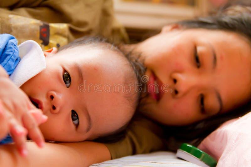 Aziatische vrouwelijke baby die met haar moeder ligt royalty-vrije stock afbeelding