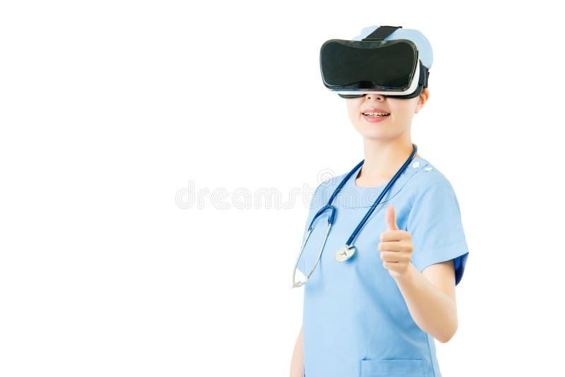 Aziatische vrouwelijke chirurgenduim omhoog met VR-hoofdtelefoonglazen stock foto's