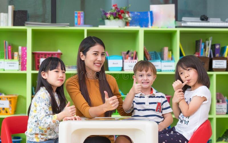 Aziatische vrouwelijke leraar en de gemengde duimen van rasjonge geitjes omhoog in klaslokaal, royalty-vrije stock foto's
