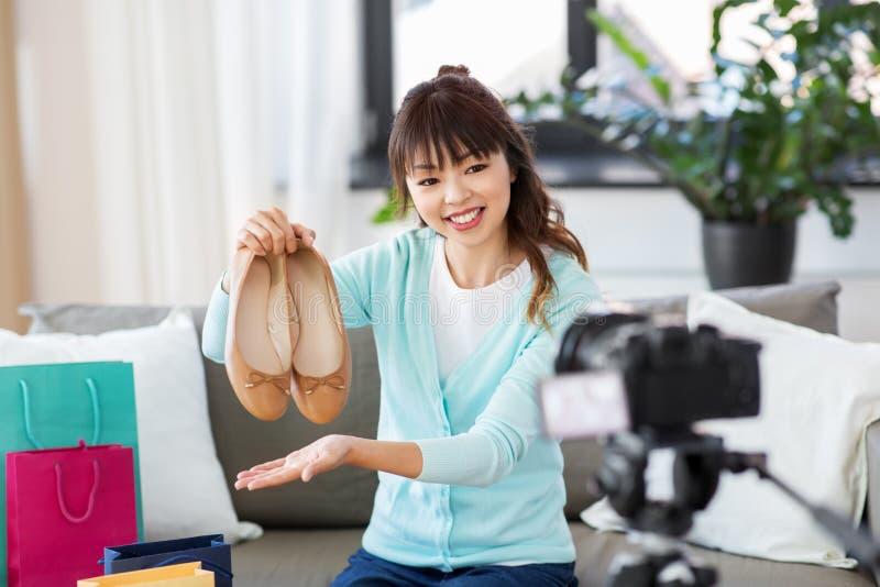 Aziatische vrouwelijke manier die blogger video van schoenen maken stock afbeelding