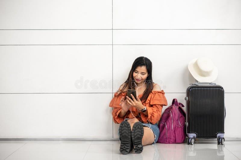 Aziatische vrouwelijke reiziger die op vlucht wachten en smartphone buiten zitkamer in luchthaven met behulp van Reis en van de m stock foto's