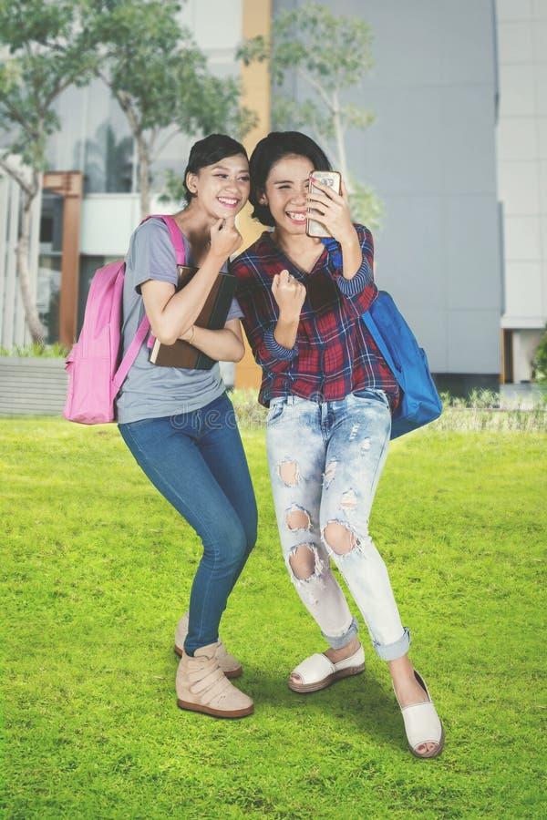 Aziatische vrouwelijke studenten die hun succes uitdrukken stock foto's