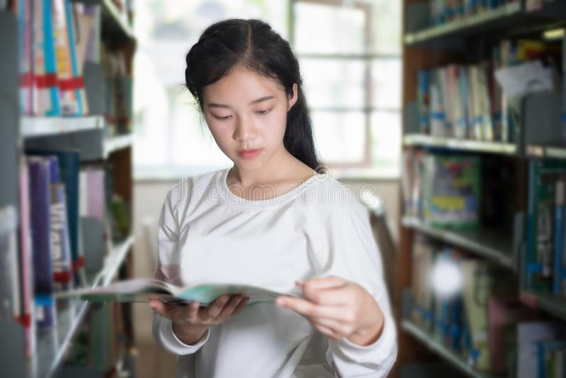 Aziatische vrouwelijke studenten die voor selectieboek houden in bibliotheek royalty-vrije stock afbeelding