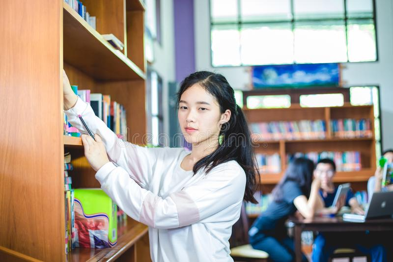 Aziatische vrouwelijke studenten die voor selectieboek houden in bibliotheek royalty-vrije stock foto's