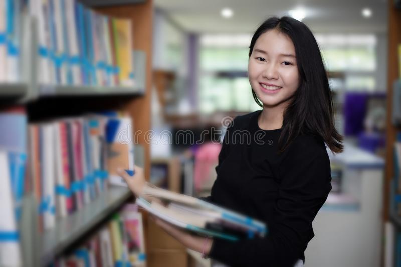 Aziatische vrouwelijke studenten die voor selectieboek houden in bibliotheek stock afbeelding