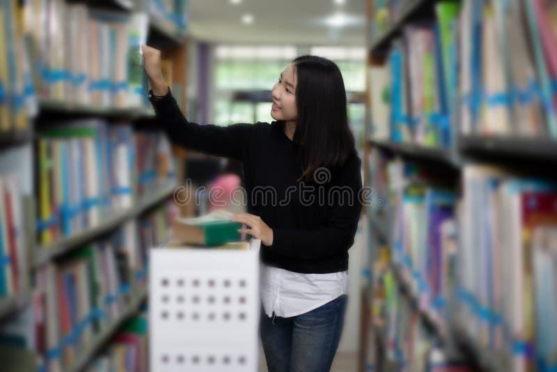 Aziatische vrouwelijke studenten die voor selectieboek houden in bibliotheek royalty-vrije stock foto
