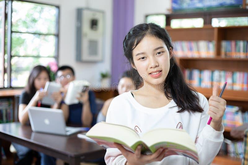 Aziatische vrouwelijke studenten die voor selectieboek houden in bibliotheek stock afbeeldingen