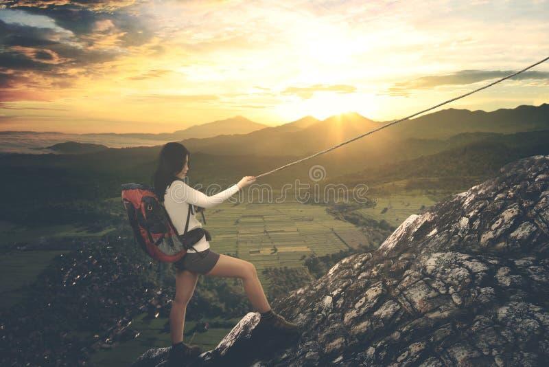 Aziatische vrouwelijke wandelaar die een steile berg beklimmen royalty-vrije stock afbeelding