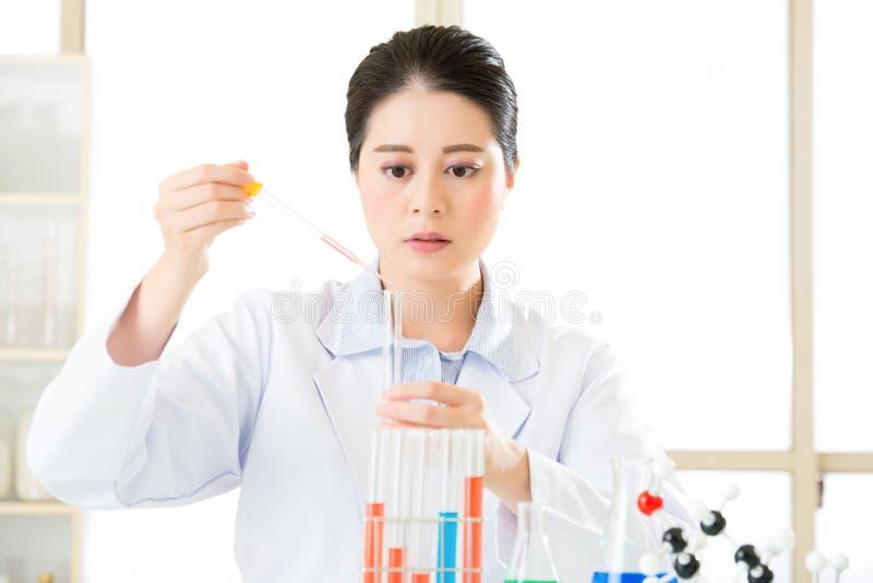 Aziatische vrouwelijke wetenschapper die wetenschappelijke grenzen met haar r breken royalty-vrije stock foto's