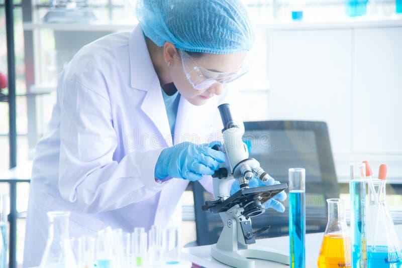 Aziatische vrouwelijke wetenschapper, onderzoeker, technicus of student voerde onderzoek of experiment uit door microscoop in lab stock afbeeldingen