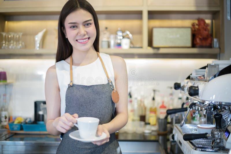 Aziatische vrouwen Barista die en koffiekop glimlachen houden en MAC gebruiken stock foto