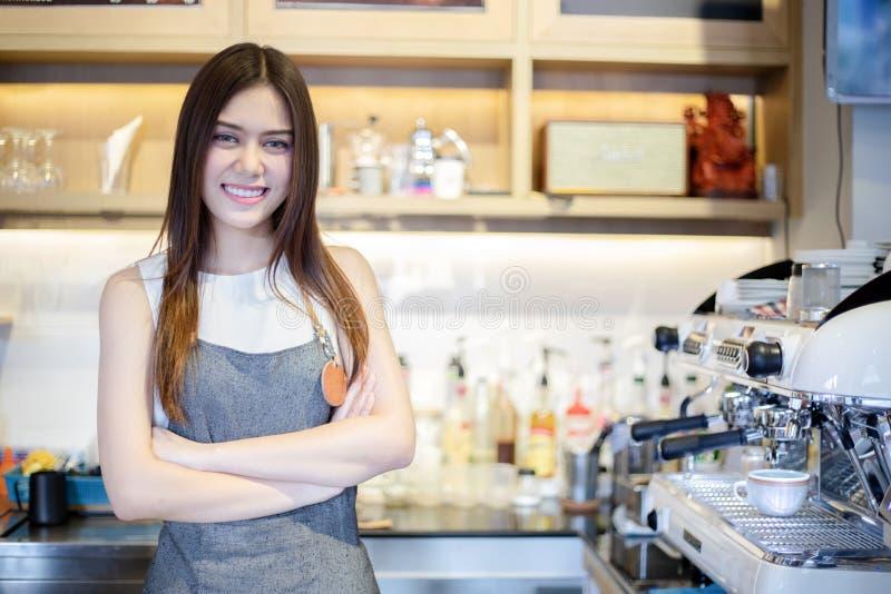 Aziatische vrouwen Barista die en koffiemachine in de teller van de koffiewinkel glimlachen met behulp van - Werkende vrouwen kle royalty-vrije stock foto