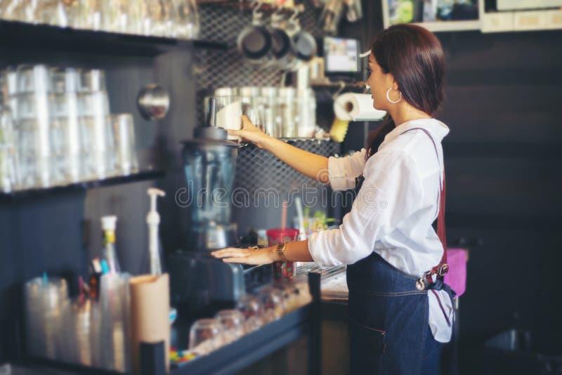 Aziatische vrouwen Barista die en koffiemachine in koffie s glimlachen met behulp van royalty-vrije stock afbeelding