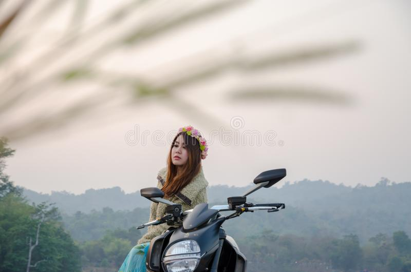 Aziatische vrouwen berijdende motor op tropisch gebied stock foto