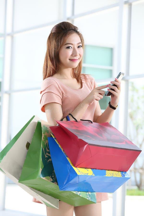 Aziatische vrouwen bij het houden van heel wat het winkelen zak stock afbeelding
