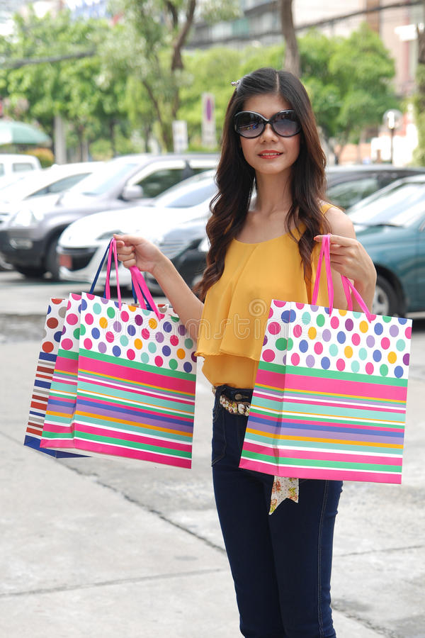 Aziatische vrouwen bij het houden van heel wat het winkelen zak in Supermarkt royalty-vrije stock afbeelding